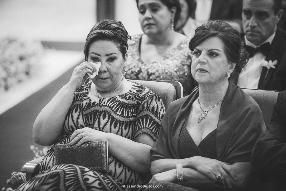 com um papel enxuga os olhos a mãe da noiva do casamento em belo horizonte bh foto enquanto observa uma das madrinhas