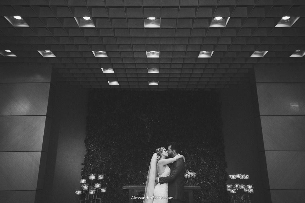 finalmente o beijo dos noivos do casamento em belo horizonte bh foto com as luzes da igreja na parte de cima