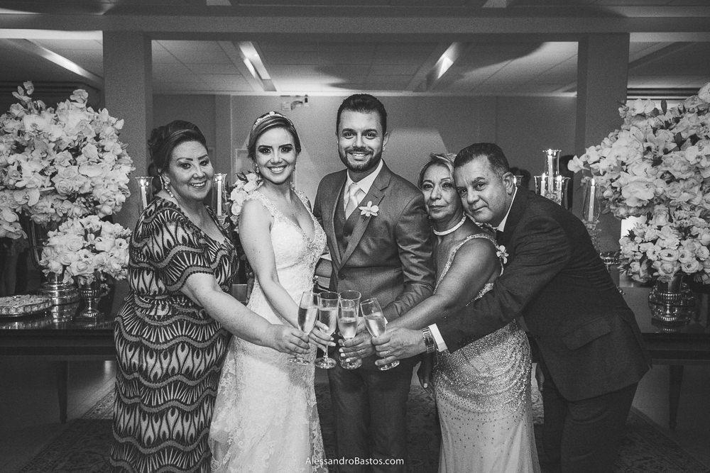 brindando estão os noivos do casamento em belo horizonte bh foto e seus pais na frente do bolo