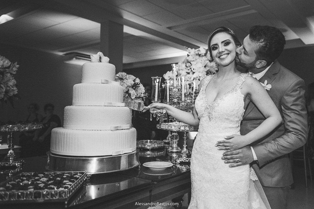 cortando o bolo estão os noivos do casamento em belo horizonte bh foto e ela a beija na bochecha