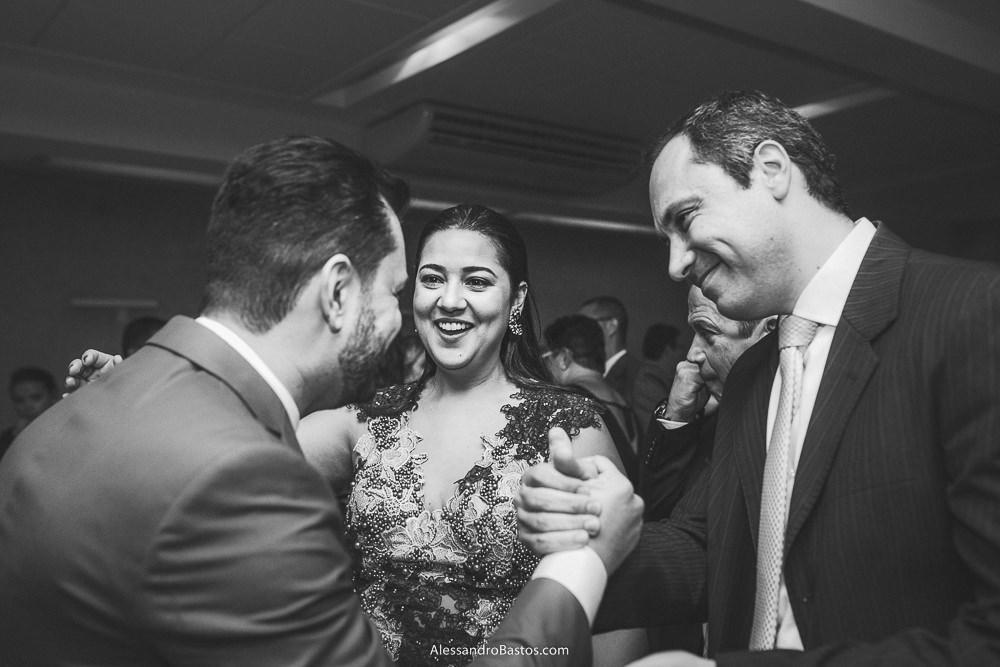 convidado aperta a mão do noivo do casamento em belo horizonte bh foto enquanto a esposa sorri