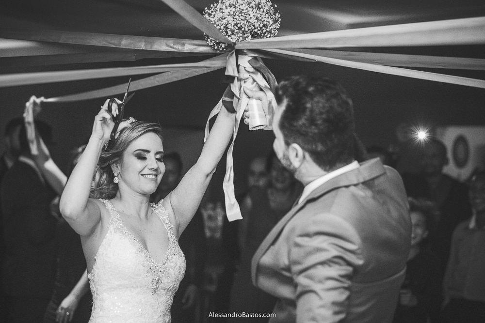 Simone noiva do casamento em belo horizonte bh foto corta o buquê de fitas com ajuda do noivo Alex