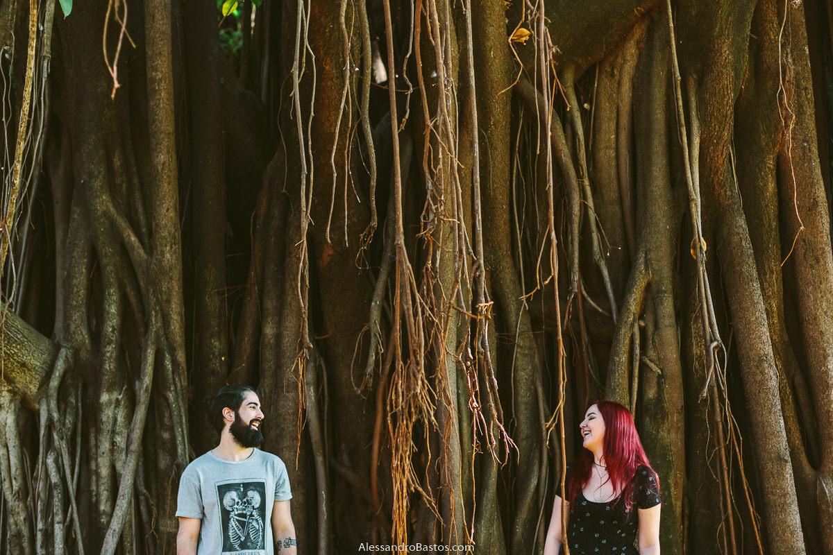 enormes raízes de uma árvore secular serve de fundo para os noivos em sessão de fotografia pré-wedding antes do casamento em bh no parque