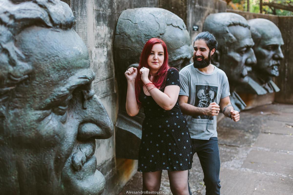 rostos de pedras são vistos com os noivos em sessão de fotografia pré-wedding antes do casamento em bh ao fundo do cenário