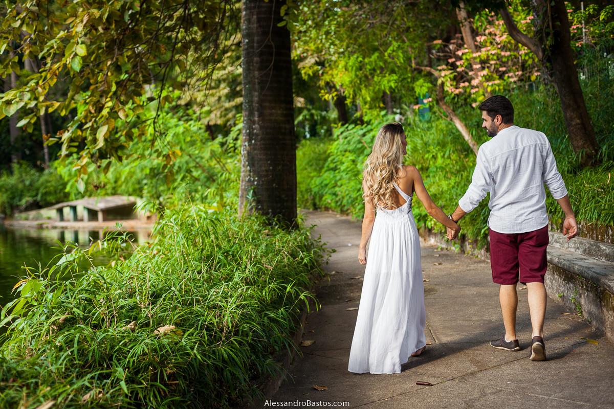 ela segura na mão dele e os noivos no ensaio pre-wedding para a fotografia do casamento em bh caminham pela mata