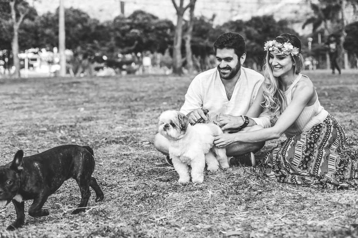 apareceu um amigo para o cão dos noivos no ensaio pre-wedding para a fotografia do casamento em bh enquanto eles estão sentandos na grama
