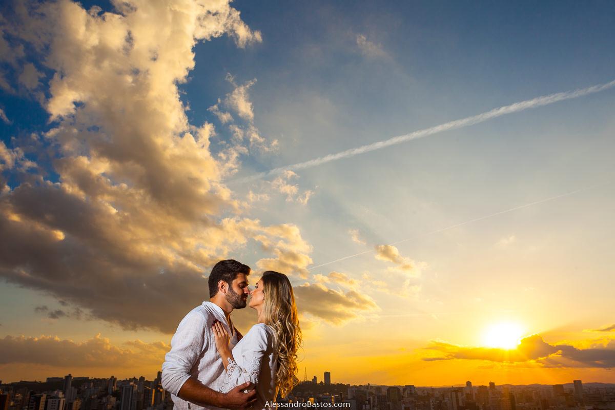 bem de frente um para o outro os noivos no ensaio pre-wedding para a fotografia do casamento em bh se beijam com o sol se pondo de cenário belíssimo