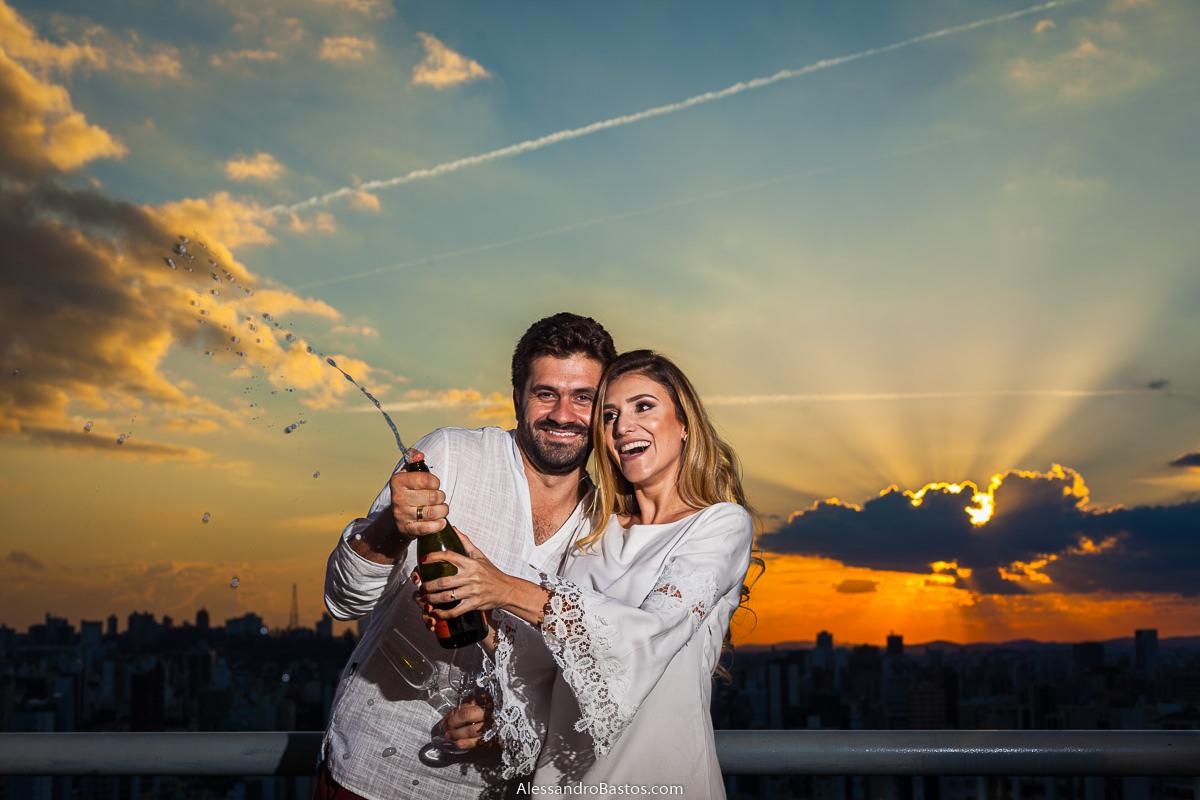 abrindo um champagne estão os noivos no ensaio pre-wedding para a fotografia do casamento em bh enquanto o sol está se pondo e cai no horizonte