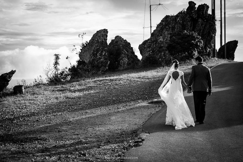 dando as mãos caminham os noivos nas fotografias após o casamento em bh com o pos-wedding na serra da piedade em preto e branco