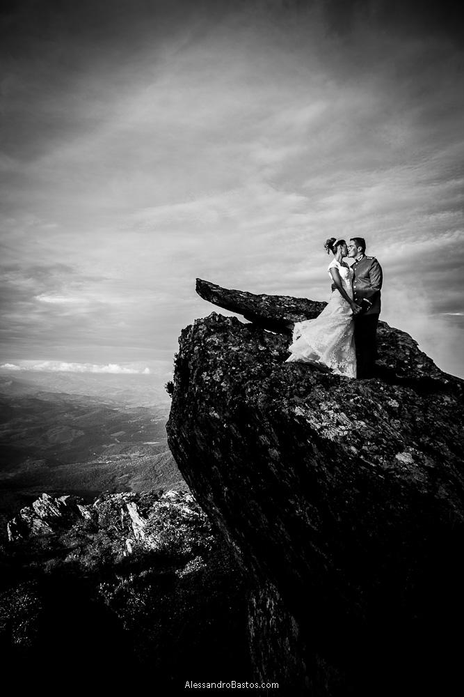 rocha acolhe os noivos nas fotografias após o casamento em bh na serra da piedade com as nuvens em preto e branco cortando o céu