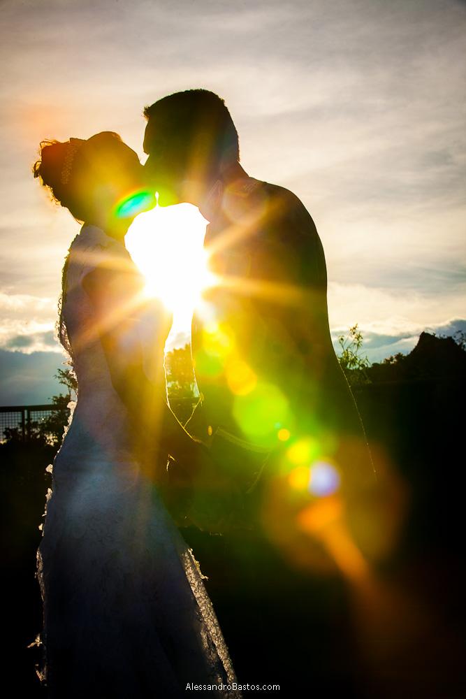 raio de luz entra na lente nas fotografias após o casamento em bh na serra da piedade e causa um efeito de estrela do sol
