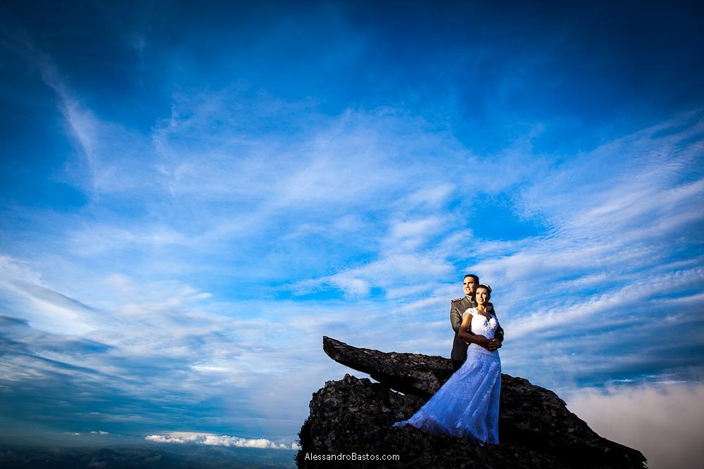 observando o horizonte estão os noivos nas fotografias após o casamento em bh na serra da piedade com o céu em um tom de azul maravilhoso