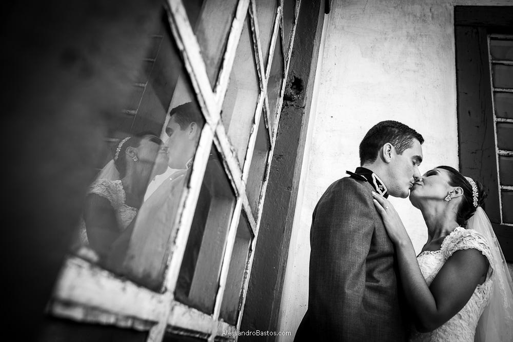 reflexo do beijo dos noivos nas fotografias após o casamento em bh na serra da piedade bem diante de uma janela