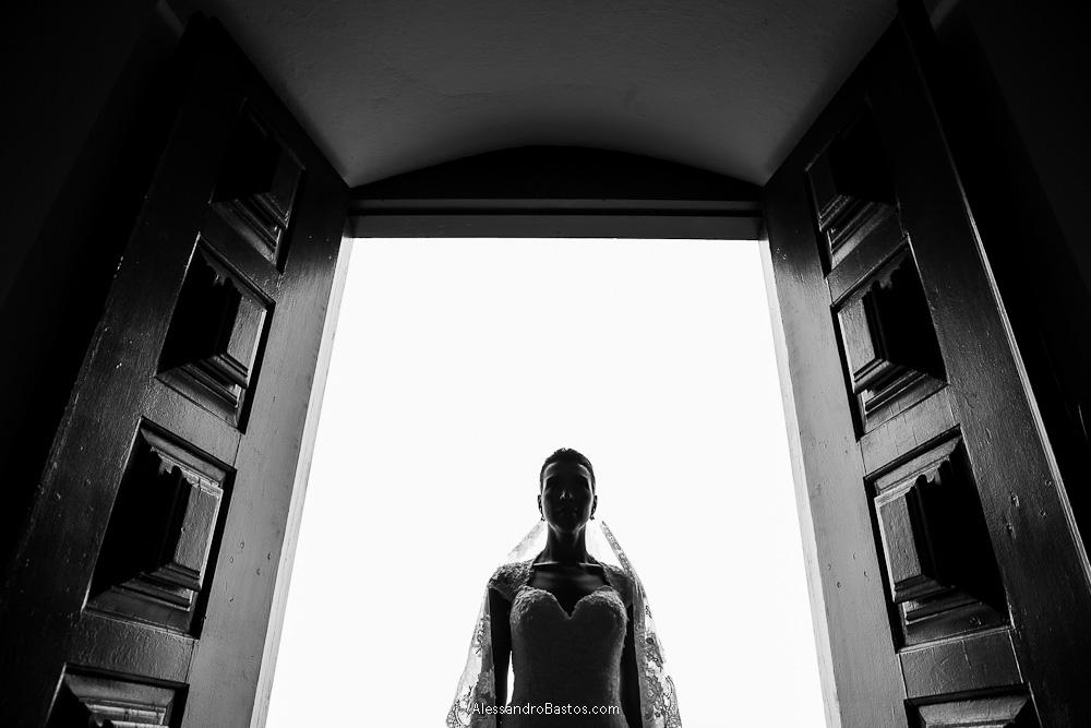 meio corpo da noiva aparece em um contra-luz nas fotografias após o casamento em bh na serra da piedade com as portas da igreja bem aberta