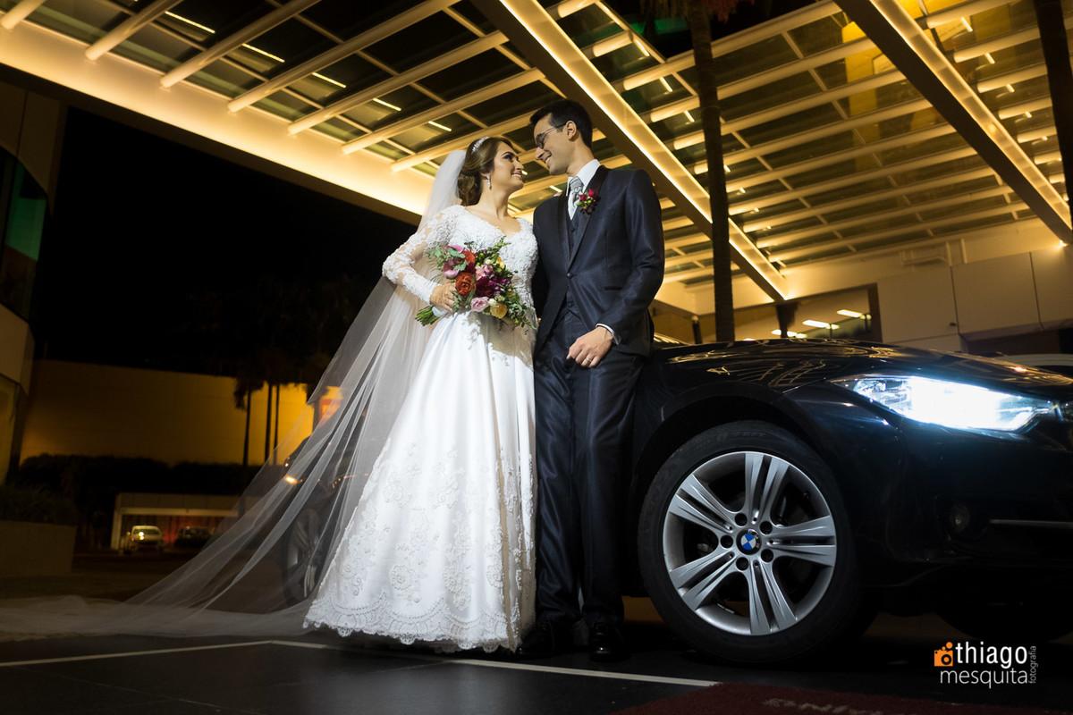 Foto dos noivos na frente do carro