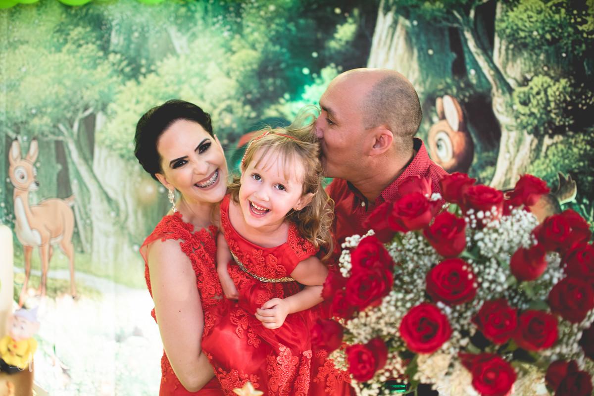 helena brincando com seus pais na mesa do bolo na sua festa de 3 anos com tema branca de neve