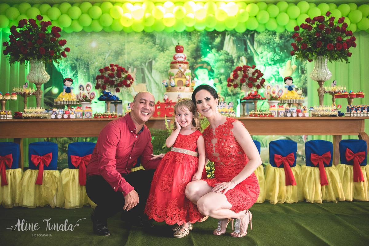 helena e seus pais abaixados na frente da decoração de branca de neve no seu aniversário de 3 anos