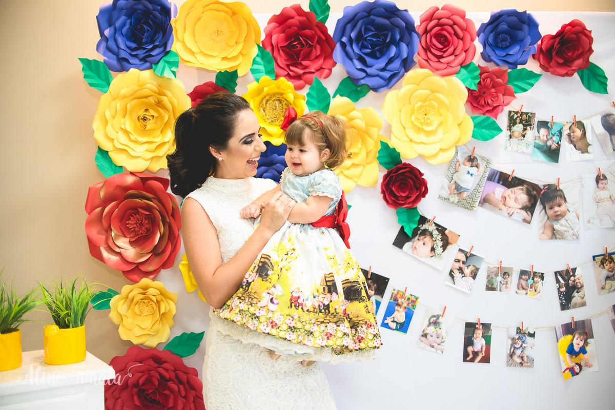 mãe e filha brincando na festa de 1 ano na frente de flores de papel e varal de fotos