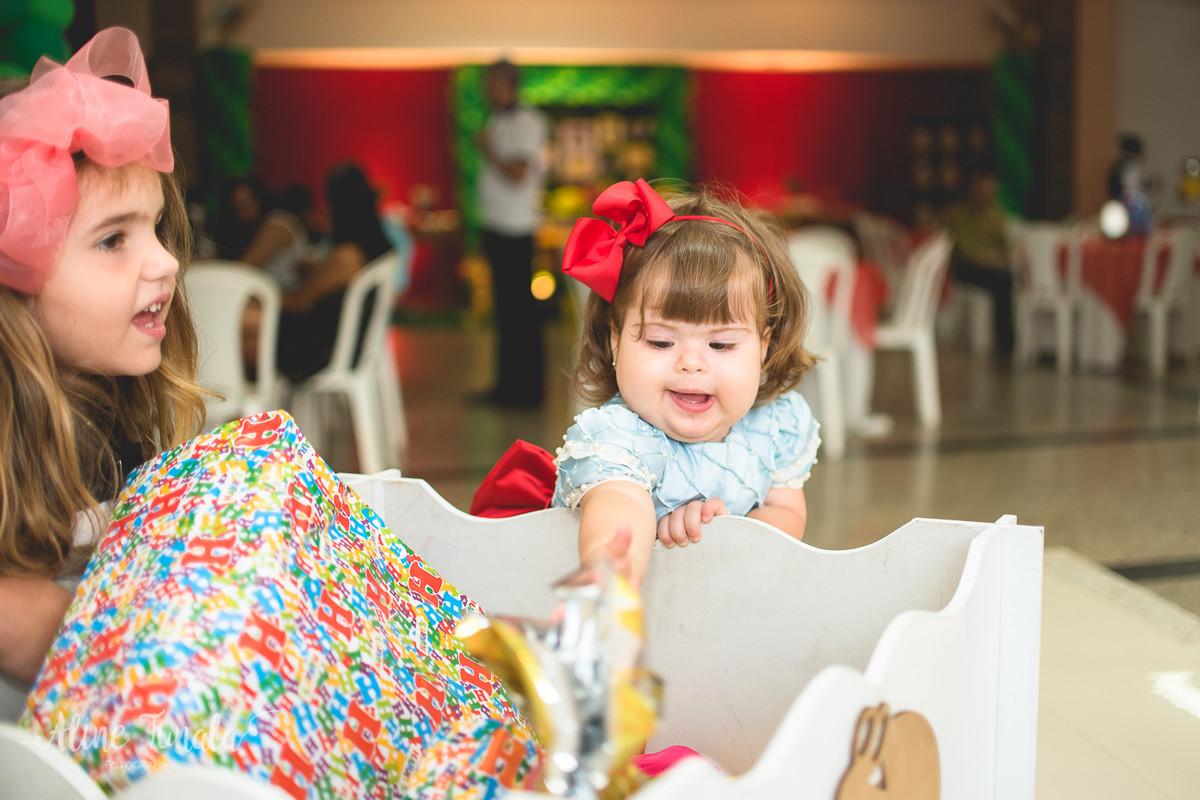 bebê mexendo nos seus presentes no seu aniversário de 1 ano
