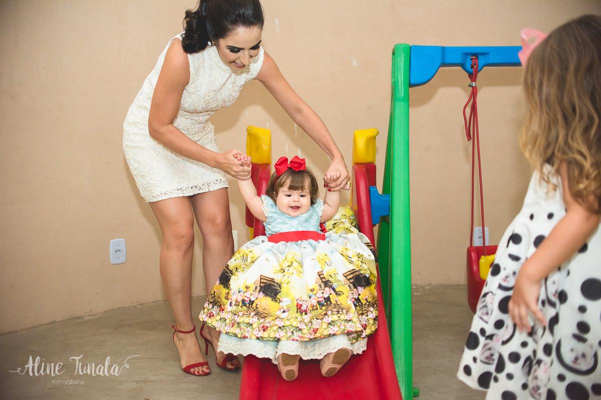bebê brincando no escorregador com sua mãe na sua festa de 1 ano
