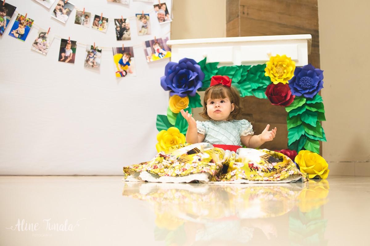 bebê na sua festa de 1 ano de branca de nece com decoração de flores de papel e varal de fotos