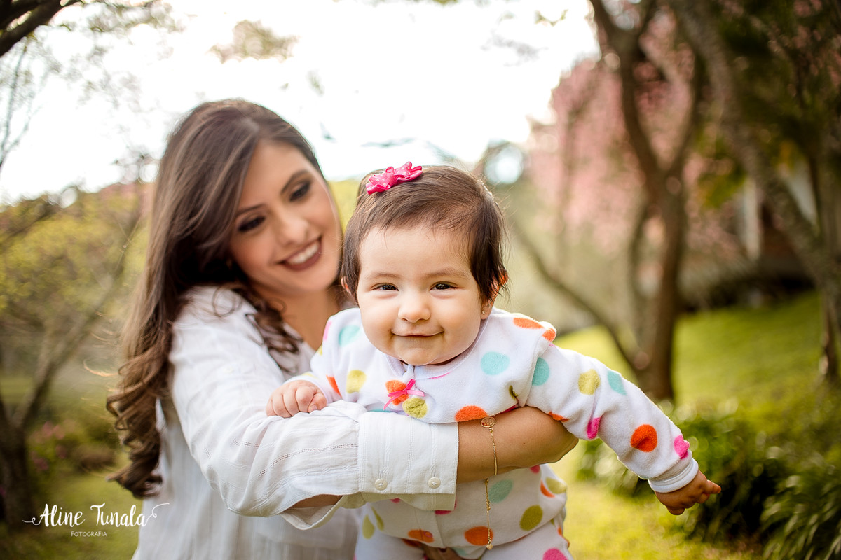 ensiao externo de 4 meses da beatriz junto com sua mãe no meio das cerejeiras floridas