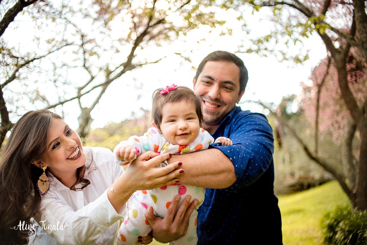 ensaio externo de acompanhamento, bebês com 4 meses junto com seus pais no fim de tarde no meio das cerejeiras floridas
