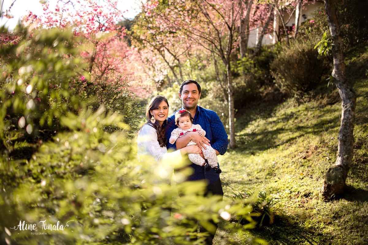 ensaio infantil de acompanhamento de bebês, beatriz com 4 meses posando com seus pais em meio as cerejeiras floridas do hotel fazenda monte verde