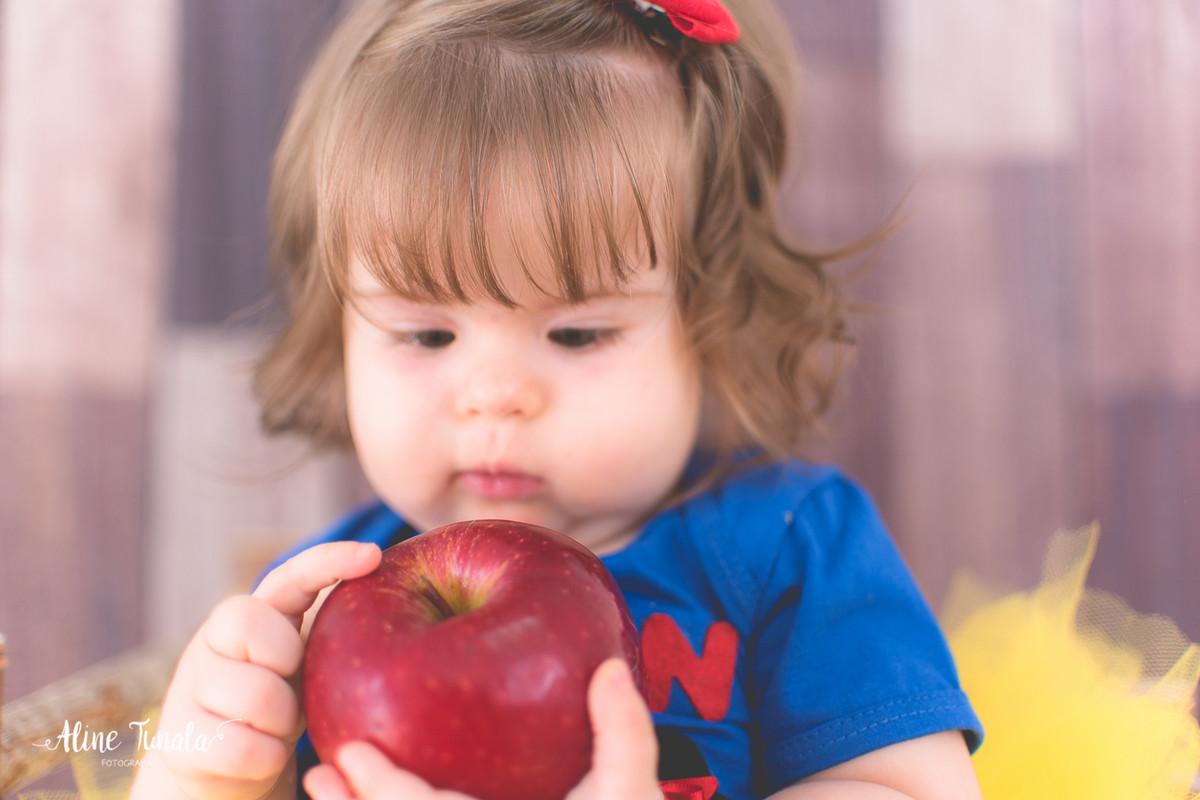 Foto temática Branca de Neve para aniversário de 1 aninho com maçãs em estúdio. Sessão infantil, ensaio infantil. 1 ano