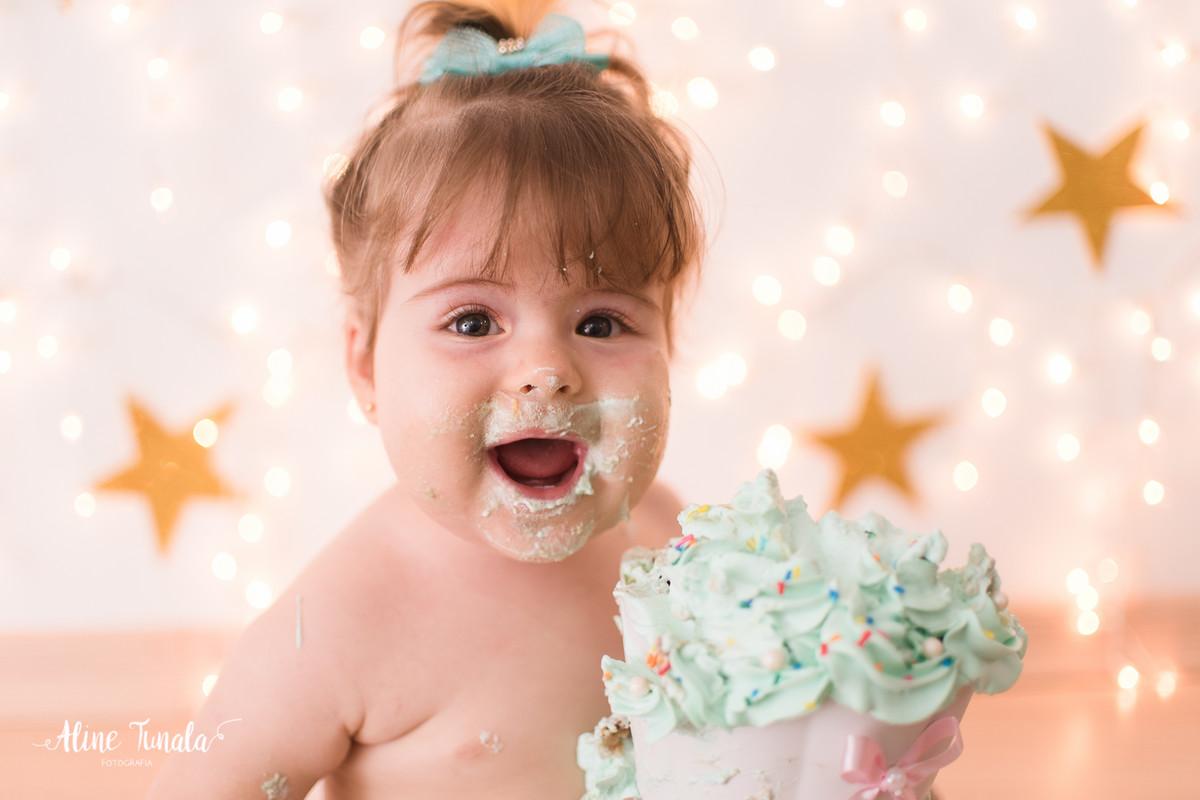 bebê sujo de bolo em seu smash the cake registrado pela fotógrafa de bebês ES Aline Tunala  numa linda cena de alegria