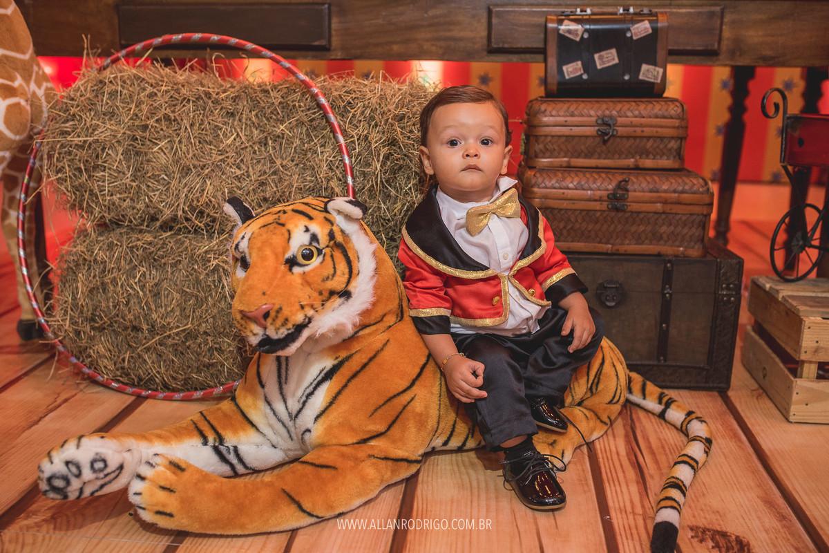 Felipe sentado no tigre no aniversário com o tema circo