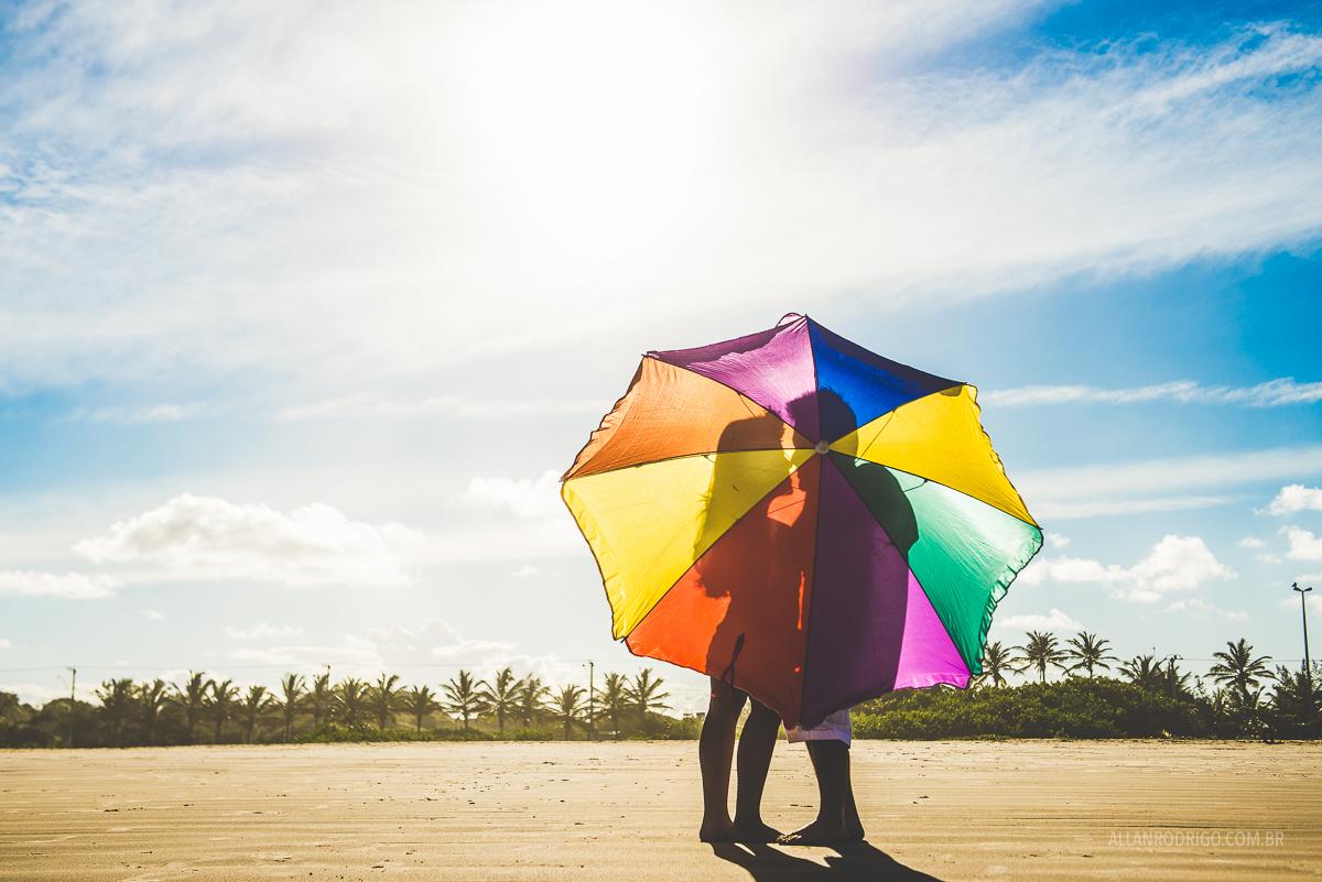 Casal na praia co guarda chuva colorido