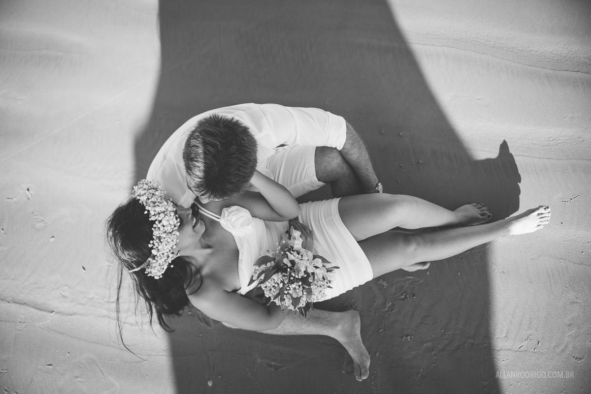 casal sentados na areia da praia