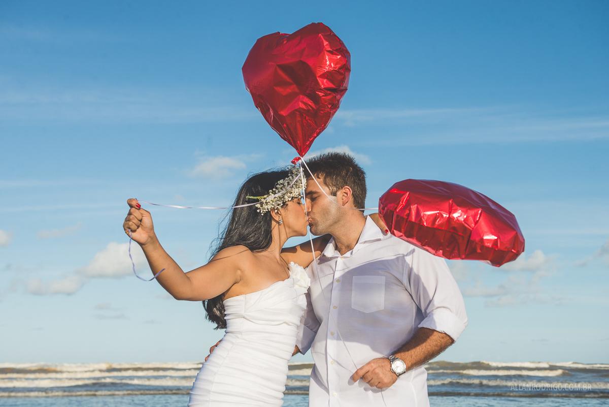 casal se beijando na praia com baloes de coração