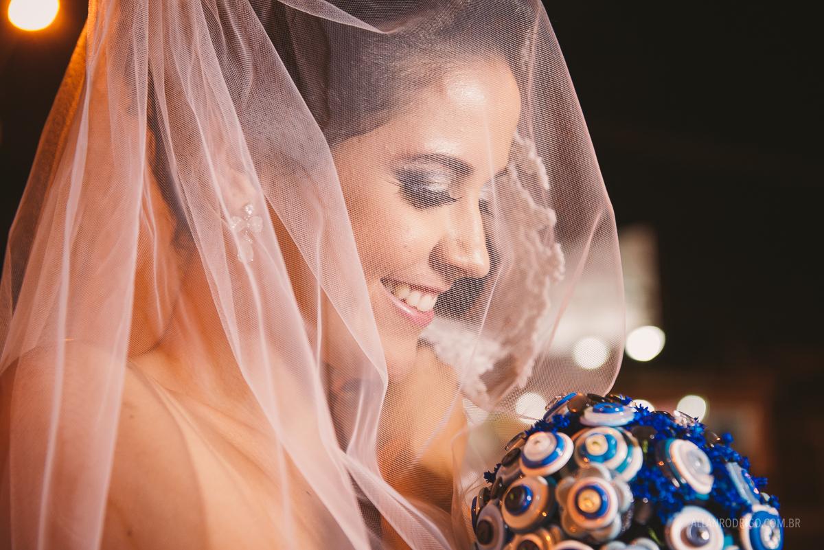 noiva sorrindo no véu segurando o buquê no click do fotógrafo de casamentos Allan Rodrigo de Aracaju SE numa linda cena de alegria