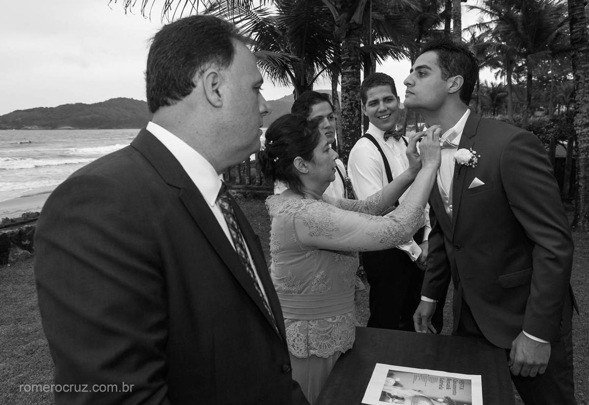 Foto do detalhe da mãe do noivo arrumando a gravata do noivo em casamento na praia