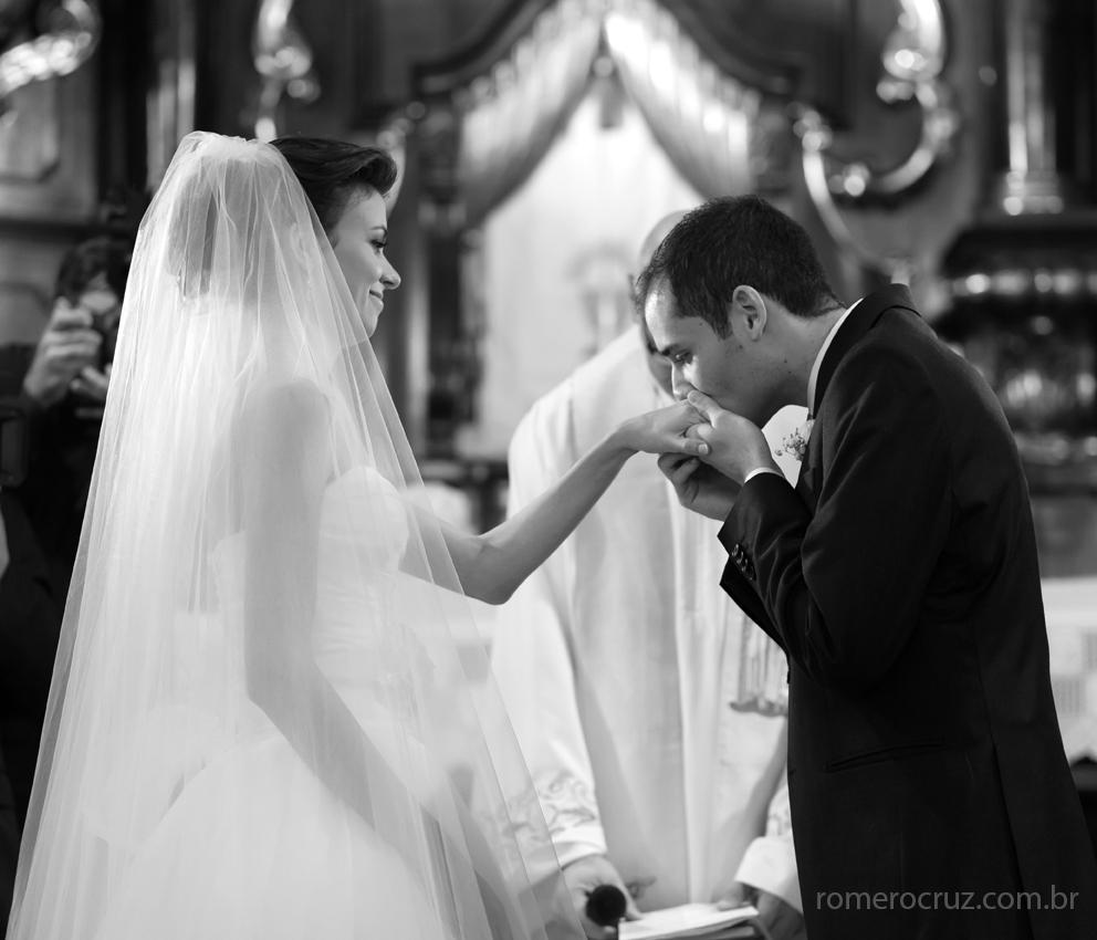No casamento na Capela da PUC em São Paulo-SP noivo beija a aliança da noiva em casamento emocionante nas lentes do fotógrafo Romero Cruz