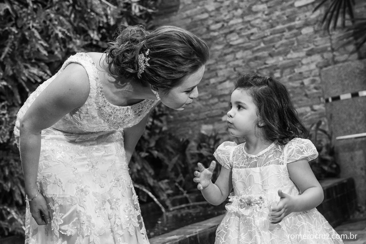 Fotografia da noiva Isabella brincando com sua daminha em casamento