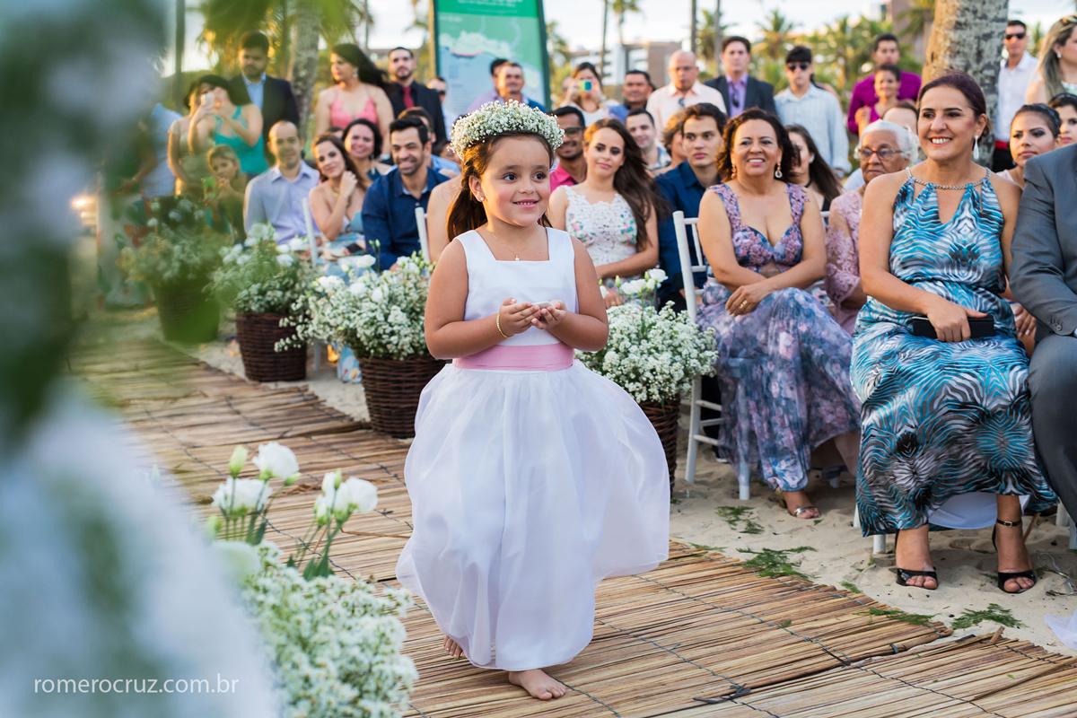 Foto da daminha levando as alianças no casamento na praia