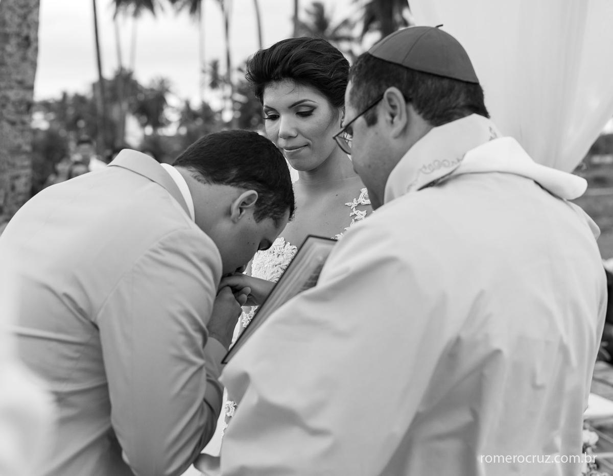 Noivo beija emocionado a mão da noiva em seu casamento registrado pelo fotógrafo Romero Cruz