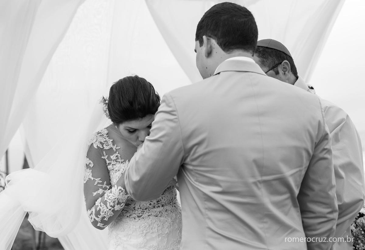 Noiva beija a aliança do noivo no casamento na praia do paiva em Pernambuco