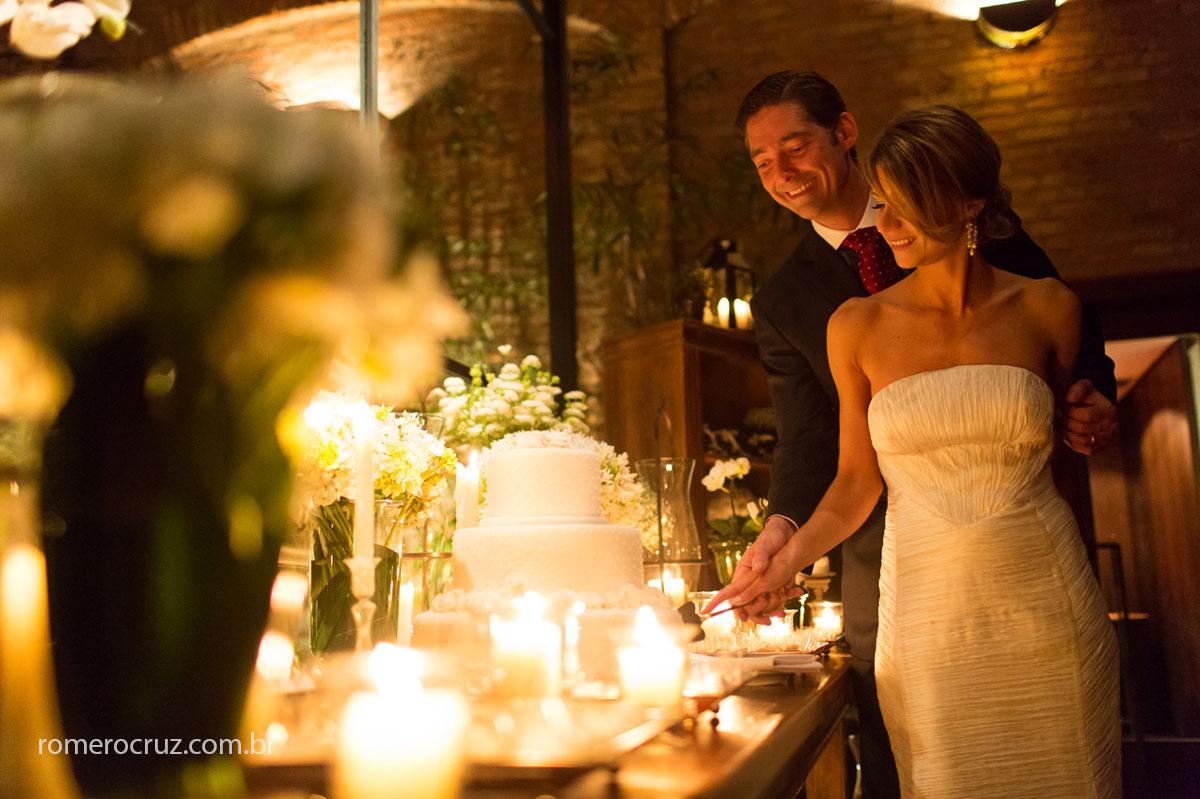 Foto do corte do bolo no lindo casamento do casal de noivos no restaurante Cantaloup em São Paulo-SP