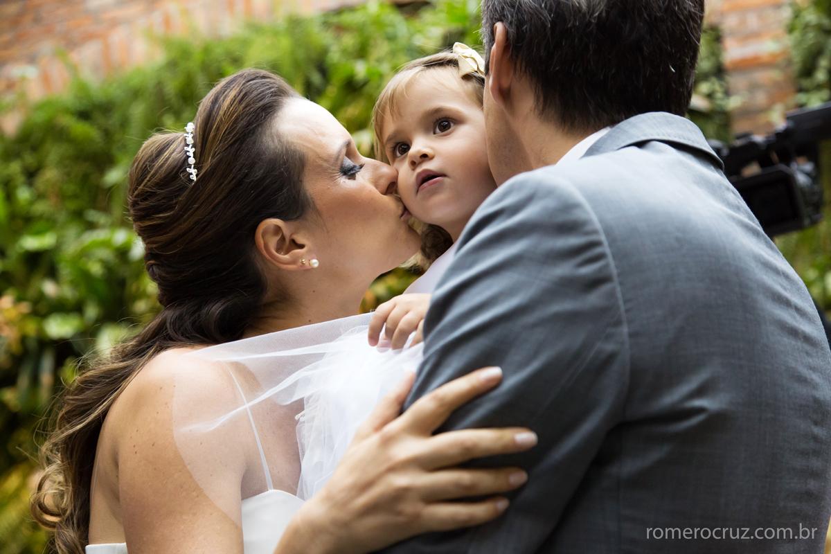 Noivos beijam a daminha no casamento