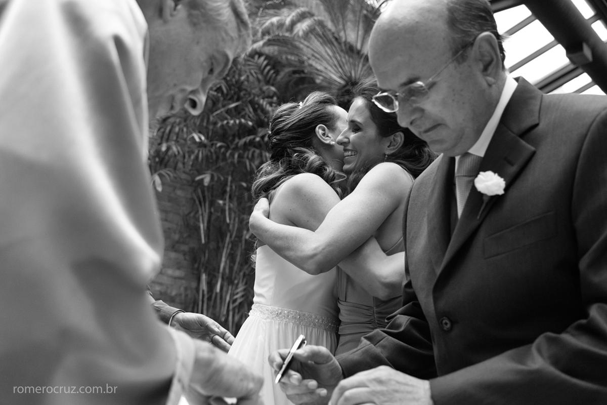 Noiva e madrinha se abraçam emocionadas em casamento