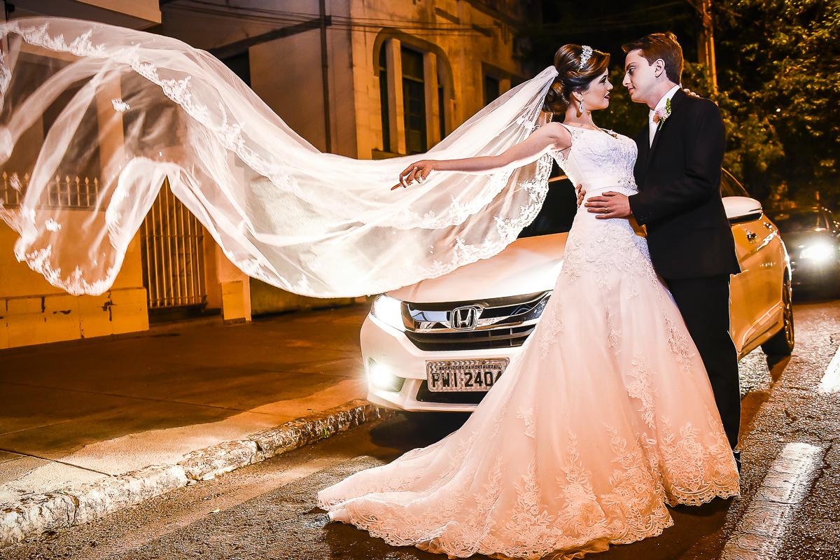 noivo abraçando e beijando a noiva e seu véu flutuando com um lindo carro atrás no click do fotógrafo de casamento Patos de Minas MG Wellington Guimarães em linda cena