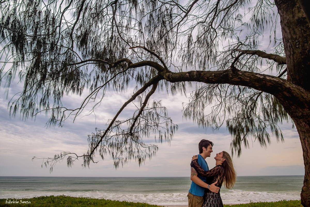 noivos sorrindo e quase se beijando embaixo da árvore na beira da praia em Florianópolis