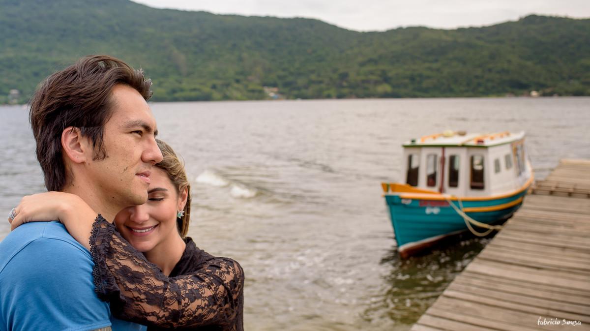 noiva no aconchego do marido em sessão fotográfica na beira da lagoa da conceição ilha da magia