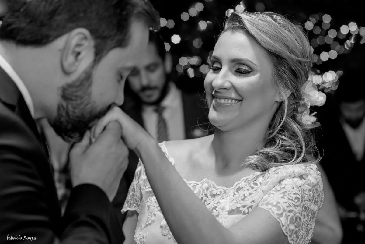 noivo beija a mão da noiva com aliança em seu mini-wedding - casamento na praia