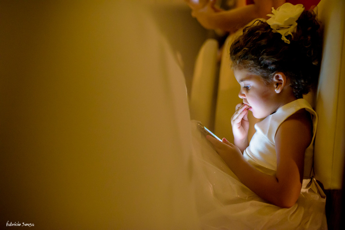 daminha brincando no celular e comendo bolacha durante a festa de casamento
