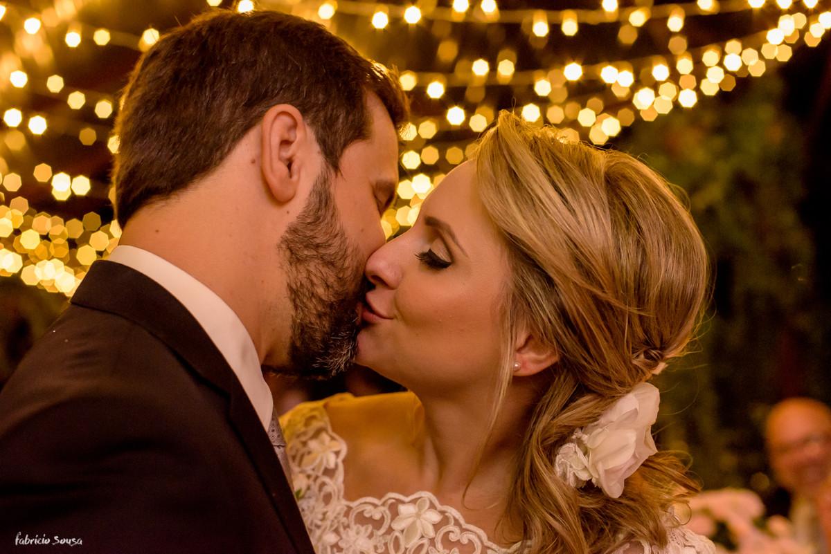 beijo apaixonado do casal com fundo de luzinhas de natal
